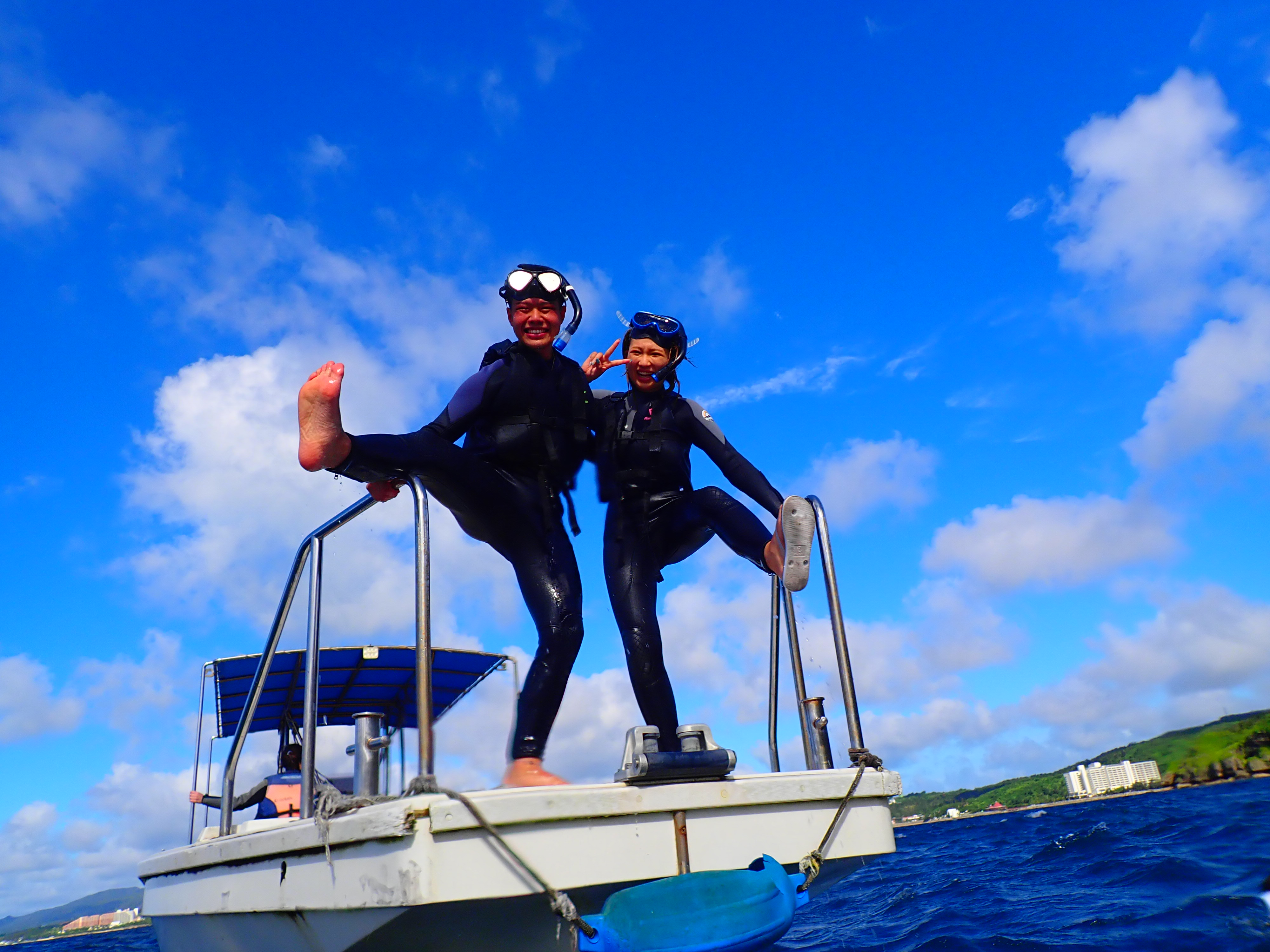 体験ダイビング前に船の上でポーズを撮るカップル