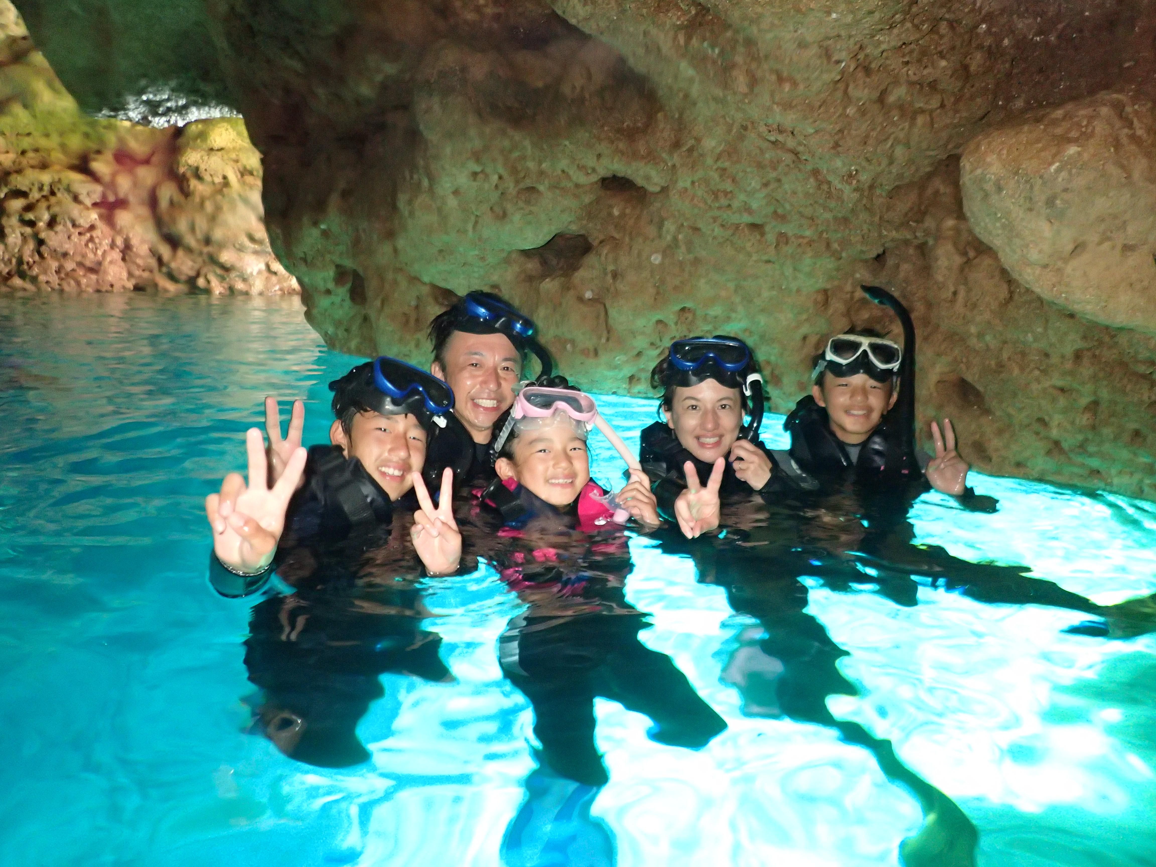 沖縄の青の洞窟でシュノーケリングツアーに参加する親子